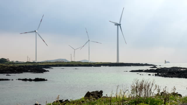 Seascape of Vertical axis wind turbine at wind power station near coastal feature