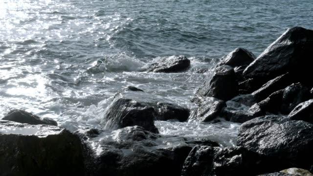 vídeos y material grabado en eventos de stock de paisaje marino con salpicaduras de agua sobre las rocas, oscilar, la luz del sol cerca punto de vista. - buena condición