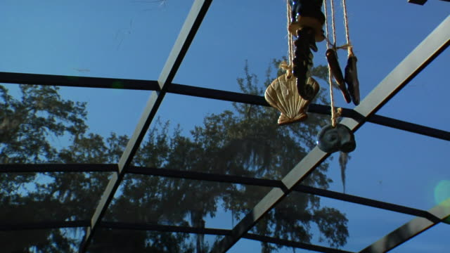 a seashell wind chime hangs from a grid. - seashell stock videos & royalty-free footage