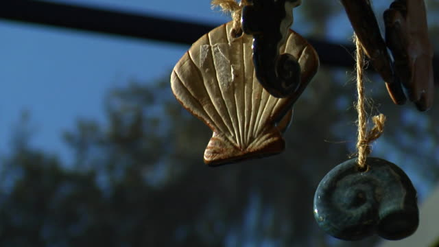 a seashell wind chime hangs from rafters. - seashell stock videos & royalty-free footage