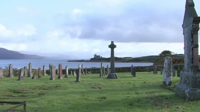 vídeos de stock, filmes e b-roll de zi seaside graveyard with duart castle in the background across the inlet / craignure, scotland, united kingdom - ilha mull