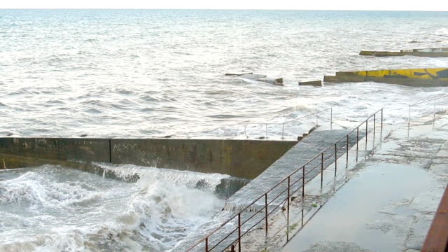 Seaside promenade with breakwaters in storm