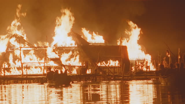 seaside village on fire, night, villagers escape in rowboats - escaping stock videos & royalty-free footage