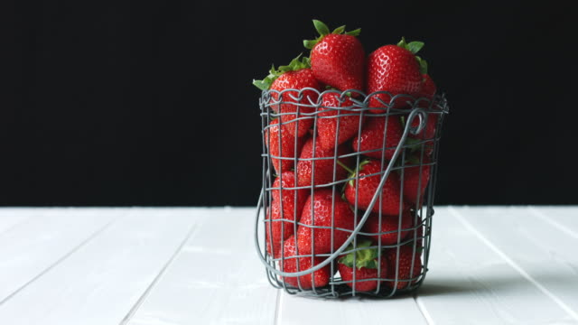 seasonal juicy red strawberries in wire basket against black background - juicy stock videos & royalty-free footage