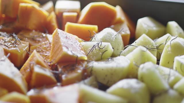 味付けされたジャガイモとカボチャは、ベーキングの準備ができています - ローズマリー点の映像素材/bロール