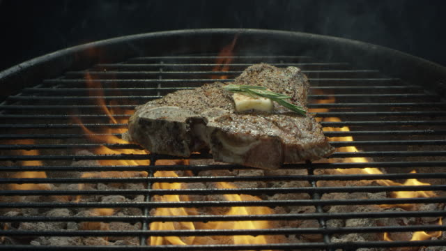 a seasoned t-bone beef steak with butter and rosemary cooks over coals on a barbecue grill - low carb diet stock videos & royalty-free footage