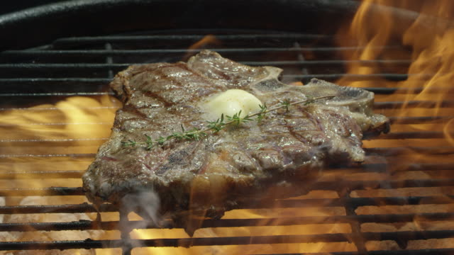 vídeos de stock e filmes b-roll de a seasoned t-bone beef steak with fresh thyme and butter cooks over a flaming bed of coals on a barbecue grill - juicy