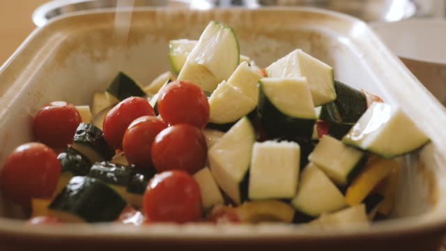 seasoning and mixing vegetable for roasting - cherry tomato stock videos & royalty-free footage
