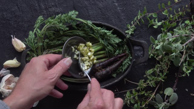 seasoning asparagus and purple carrots for roasting in a cast iron skillet. - herbs stock videos and b-roll footage