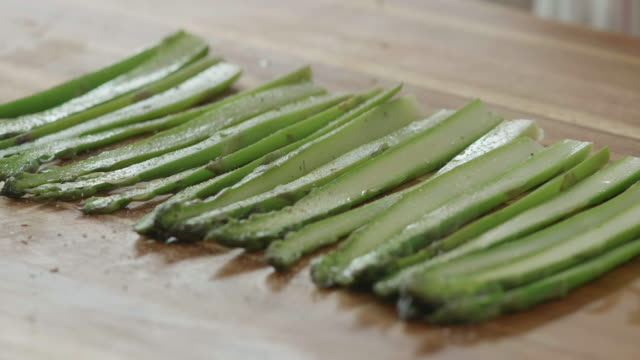 seasoning boiled asparagus on wooden chopping board - chopping board stock videos & royalty-free footage