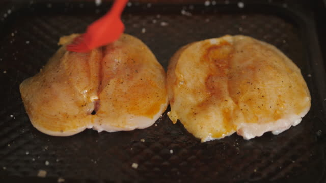 vídeos de stock e filmes b-roll de seasoning chicken breast for roasting - marina