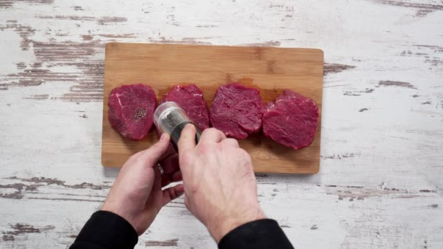 seasoning fresh chunk of the deli piece of beef with sea salt and grounded spicy peppers. - raw footage stock videos & royalty-free footage