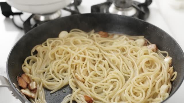 seasoning pasta on a frying pan - garlic stock videos & royalty-free footage