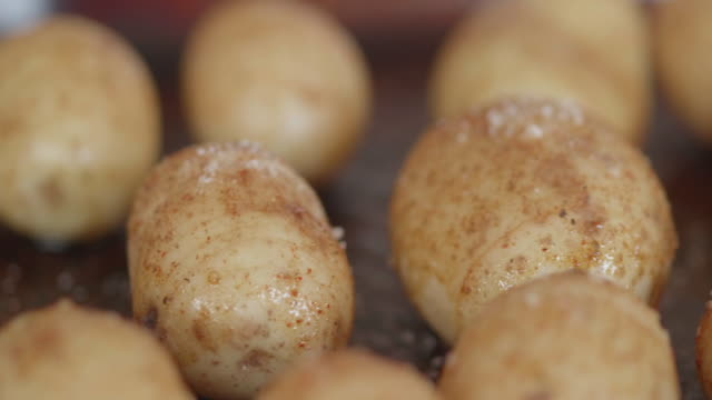seasoning prepared hasselback potatoes for roasting - potato stock videos and b-roll footage