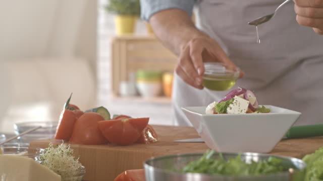 vídeos y material grabado en eventos de stock de condimentar la ensalada con aceite de oliva - cultura mediterránea