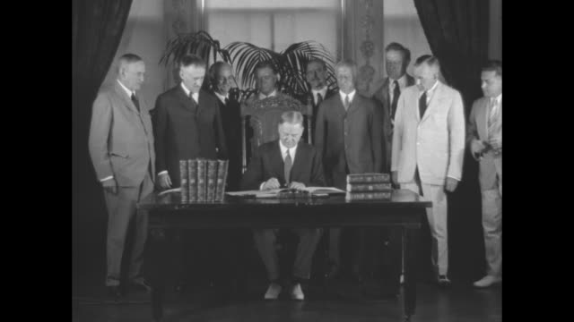 Seated at a desk with bound books in the East Room of the White House Pres Herbert Hoover signs the Treaty for the Limitation and Reduction of Naval...