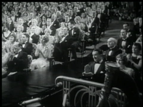 b/w 1929 seated audience in formalwear on either side of aisle clapping in theater / feature - formal stock videos & royalty-free footage