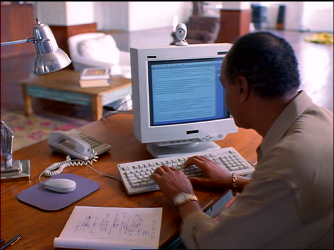 rear view seated black man looking at papers + typing into computer at desk at home - 1998 stock-videos und b-roll-filmmaterial