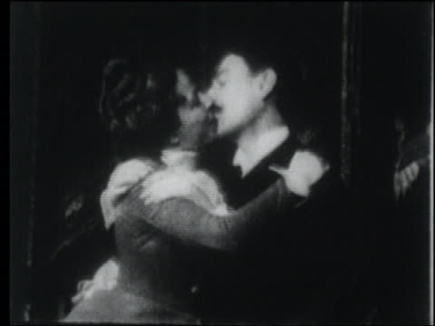 b/w 1903 seated couple hugging, kissing + smiling repeatedly - 1903 stock-videos und b-roll-filmmaterial