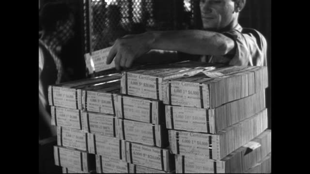/ seated female worker stacks freshly printed and cut one dollar bills / male workers stack wrapped bundles of silver certificates / man shakes his... - us currency stock videos & royalty-free footage