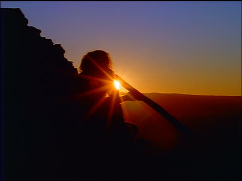 silhouette seated male aborigine playing a didgeridoo / sunset in background / blue mountains, australia - australian aboriginal culture stock videos and b-roll footage
