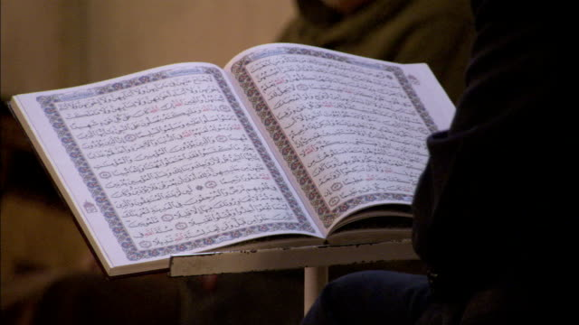 A seated man reads from the Qur'an. Available in HD.