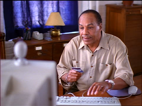 Seated smiling Black man reads from credit card + types on computer