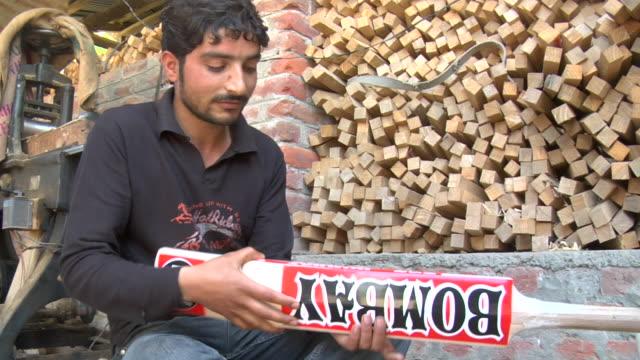 vídeos y material grabado en eventos de stock de cu seated young man applying 'bombay' label to cricket bat / bijbehara, jammu and kashmir, india - bate de críquet