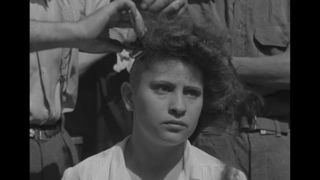 seated young woman is having her thick hair cut with metal clippers upset woman takes seat she rubs newly bald head men gather around woman being... - hair clipper stock videos & royalty-free footage
