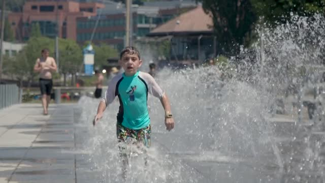 stockvideo's en b-roll-footage met seattle residents try to keep cool at the beach and under fountains, and a market closes early as people adapt to a heatwave - washington state