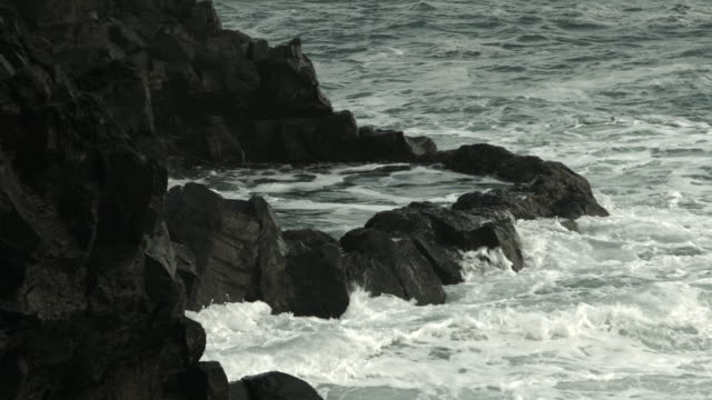seawater flows into a large rockpool on the coastline of the reykjanes peninsula in iceland. - gezeitentümpel stock-videos und b-roll-filmmaterial