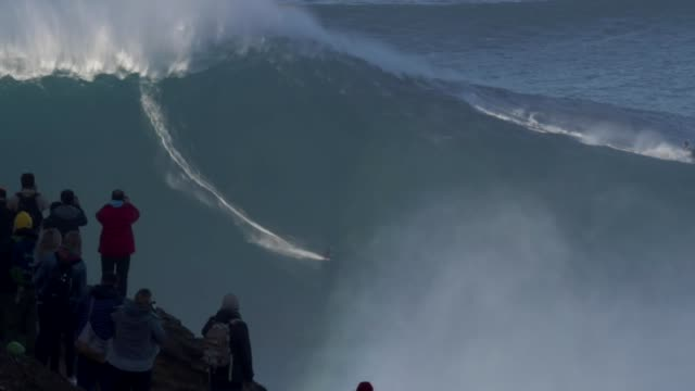 sebastian steudtner rides giant wave in nazare, portugal - largo descrizione generale video stock e b–roll