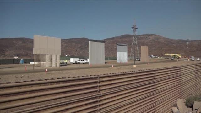 secciones de un muro hecho con concreto y acero algunas con clavos en la parte superior permanecen cerca de la frontera entre estados unidos y mexico - concreto stock videos & royalty-free footage