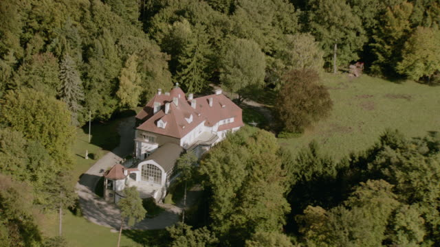 AERIAL Secluded estate mansion with turret, dormers, and veranda, on lawns in heavily wooded area