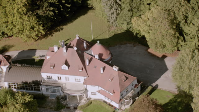 stockvideo's en b-roll-footage met aerial secluded estate mansion with turret, dormers, and veranda, on lawns in heavily wooded area - breedbeeldformaat