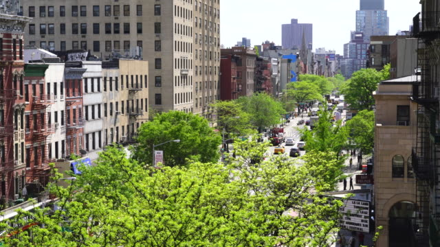 Second Avenue traffic goes through among the line of fresh green trees at East Village Manhattan New York. Rows of residential buildings surround the Second Avenue.