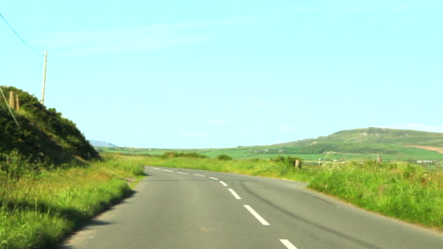 vidéos et rushes de second driving clip along quiet country road in north wales, uk video shot through windscreen. - route de campagne