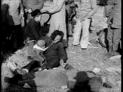 stockvideo's en b-roll-footage met second sinojapanese war / woman with child crying by dead body after japanese attack of shanghai / soldier carrying injured child / wounded girl... - 1937