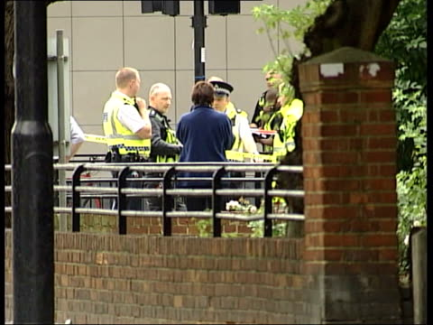 roundup oval station gv oval tube station tilt down to police cordon and bv police car ls police standing in group talking wall in f/g male... - t in the park stock-videos und b-roll-filmmaterial