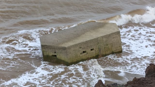 a second world war pill box on the beach near aldbrough on yorkshires east coast, uk. it was originally constructed on the cliff tops but has collapsed into the sea as the coastline rapidly erodes back. the coast is composed of soft boulder clays, very vu - bomb shelter stock videos & royalty-free footage