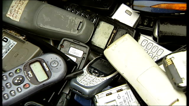 secondhand mobile phones sold by pawnbrokers without personal data being wiped ext close shots of second hand mobile phones falling into container... - gloucestershire stock videos and b-roll footage