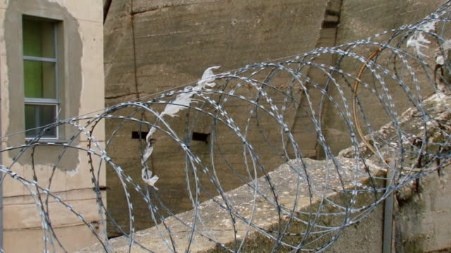 secret facility behind a concrete wall and barbed wire - fence stock videos & royalty-free footage