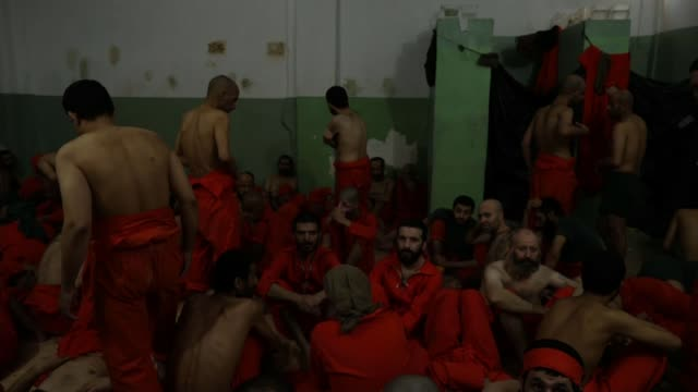 vidéos et rushes de secret prison housing islamic state prisoners; syria: int hatch in prison cell door opened and islamic state prisoners seen crowded inside, all... - prison