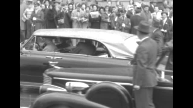 VS Secret Service officers walk alongside a slowly moving convertible with its top up the car bears US Pres Harry Truman and the Netherlands' Queen...
