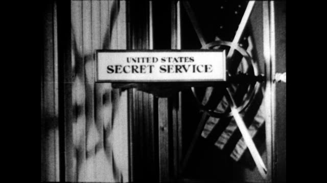 stockvideo's en b-roll-footage met secret service sign on door / frank j wilson head of secret service seated and writing at his desk / outline of the united states with dashed line... - geheime dienstagent