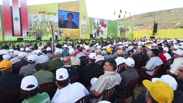 secretary general hasan nasralla of hezbollah speaks on wide screen monitor as crowd listens applauds waves flags in lebanon - hezbollah stock videos & royalty-free footage