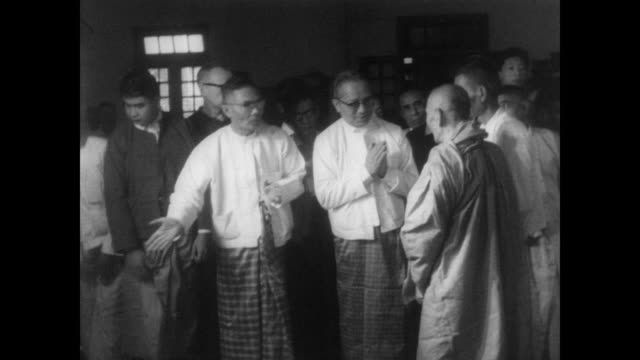 UN Secretary General U Thant in traditional Burmese costume hosts Buddhist monks for a ceremonial meal after meeting with North Vietnamese leaders in...