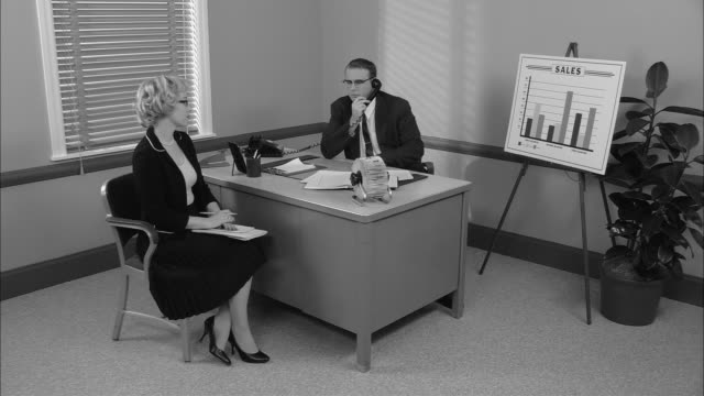 b/w ws secretary getting up from chair in boss's office and walking out as he talks on phone/ new york city - sekretärin stock-videos und b-roll-filmmaterial