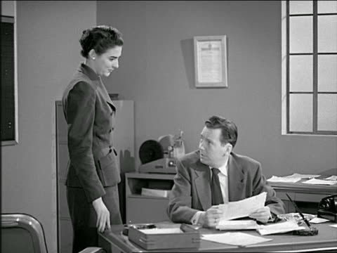 b/w 1953 secretary handing papers to businessman at desk / he hands her more + she exits - sekretärin stock-videos und b-roll-filmmaterial