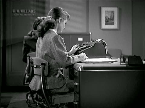 B/W 1948 secretary in office using adding machine + writing down data / other woman in background